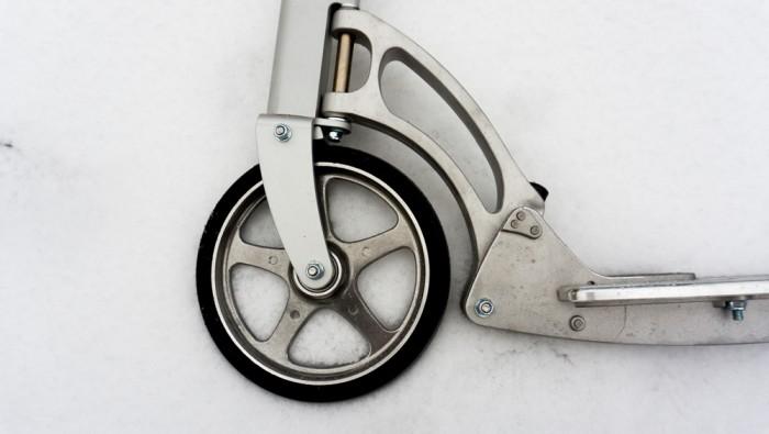 """Přední kolečko. Malý černý """"čudlík"""" napravo ohybu je jednoduchým, praktickým a účinným skládacím mechanismem"""